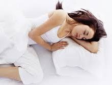 A woman sleeping on her side with her arm folded beneath her head