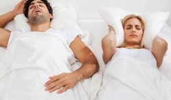 Two people laying in a bed one snoring and the other with a pillow around her head
